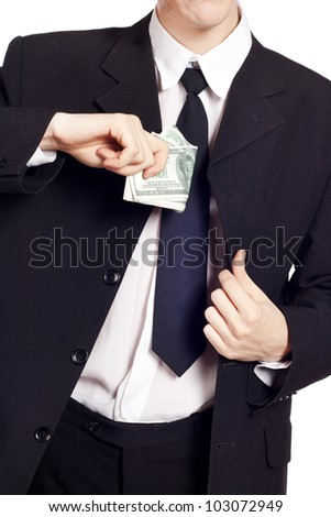 Businessman is putting money in his pocket - stock photo
