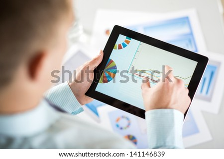 Businessman is reading business graphs and charts