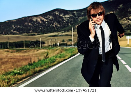 Businessman is running on the highway and talking on a mobile phone. Business struggle concept. - stock photo