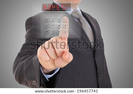 Businessman is setting code of security alarm system - stock photo