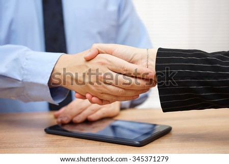 Businessman is  shaking hands with  partner after review of operations on the tablet pc - stock photo