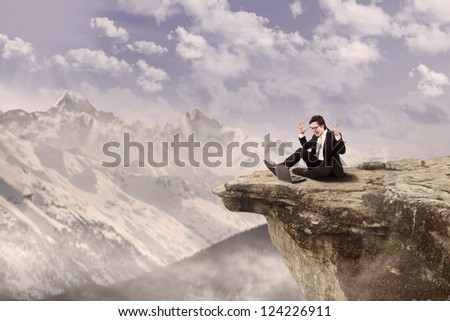Businessman is sitting happily while working on his laptop on top of a mountain