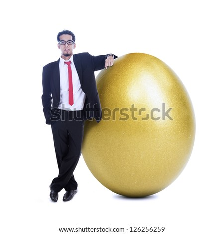 Businessman is standing beside a big golden egg on white background - stock photo