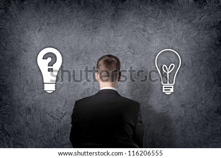 Businessman is standing in front of two direction signs. - stock photo
