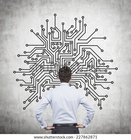 Businessman is standing in front of wall sketch of microchip picture. - stock photo