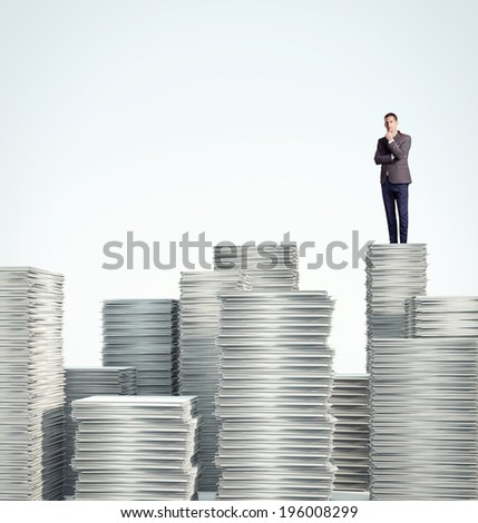 Businessman is standing on a pile of blank documents - stock photo