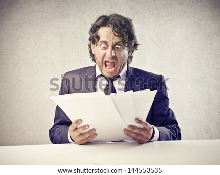 businessman is surprised by reading the documents - stock photo