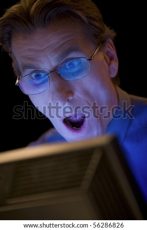 Businessman is surprised, looking at the computer monitor - stock photo