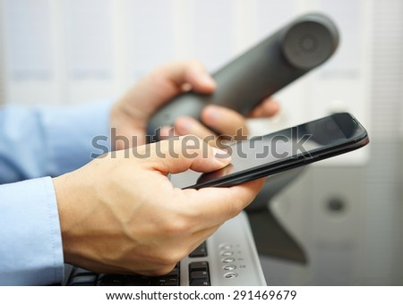 businessman is using  smart mobile phone and land line telephone at the same time