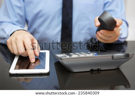 businessman is using tablet pc and calling support - stock photo