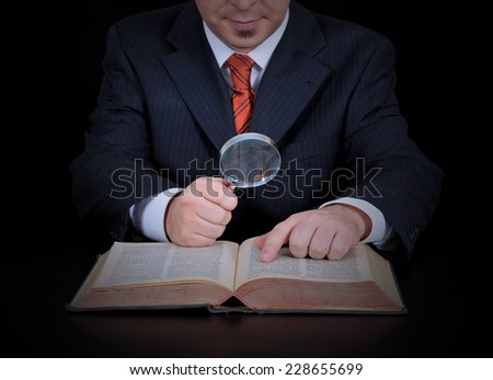 businessman is using the magnifying glass on the black background