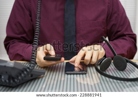 businessman is using two mobile phones and land line telephone at the same time - stock photo