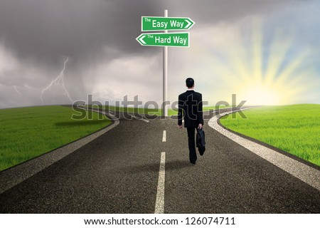 Businessman is walking on the easy way lane with stormy background - stock photo
