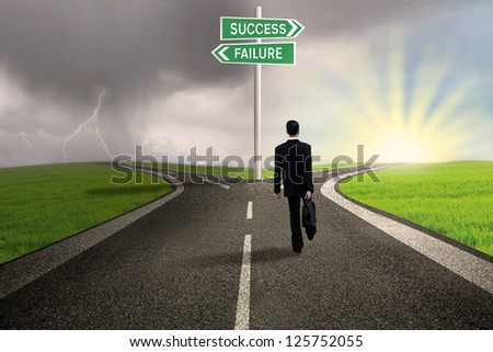 Businessman is walking on the road with a sign of success or failure - stock photo
