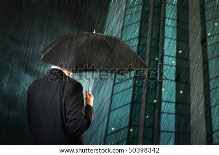 Businessman is walking toward a corporate building, holding an umbrella. Hard rain falling.
