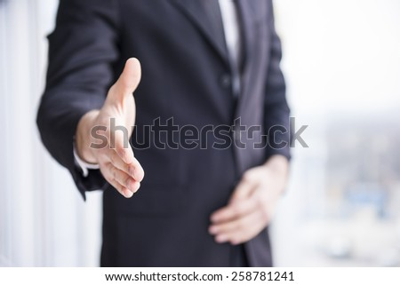 Businessman is wearing in suit, handshake to you. - stock photo