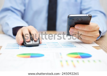 businessman is working on computer and using mouse and using smart mobile phone at the same time on the desk with full of charts and reports - stock photo