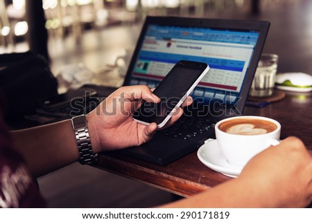 Businessman is working with laptop, holding a mobile phone in coffe shop and drinking coffe. - stock photo