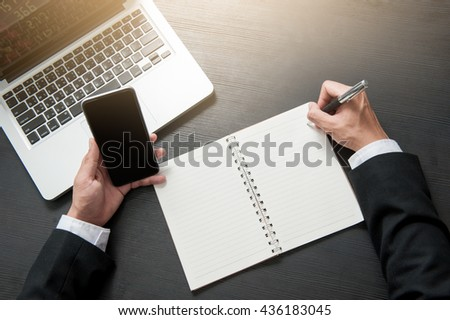 Businessman is writing a book on statistics. And computer-based on Work desk. - stock photo