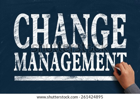 Businessman is writing Change management text on blue chalkboard. - stock photo