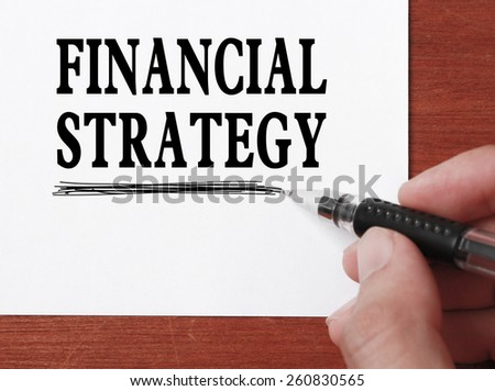 Businessman is writing Financial strategy text on white paper. - stock photo