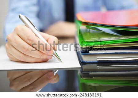 businessman is writing on document and a lot of documentation is waiting to be reviewed - stock photo