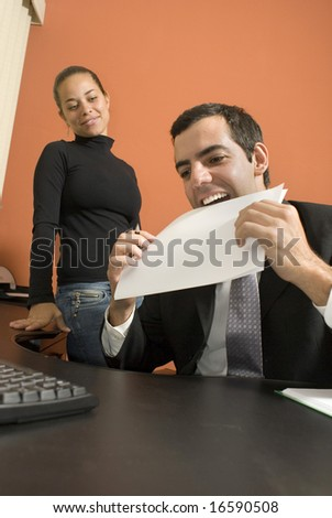 Businessman jokes around by putting a paper in his mouth as his co-worker watches. Vertically framed photo - stock photo