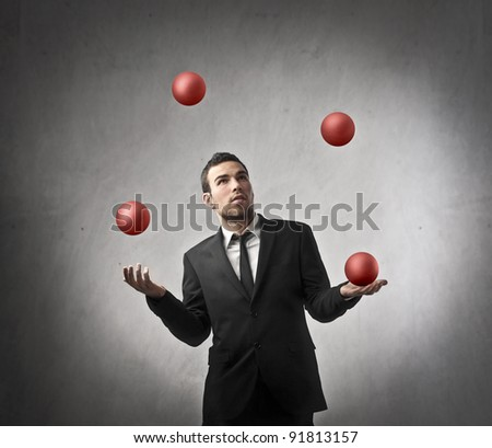 Businessman juggling with some balls - stock photo