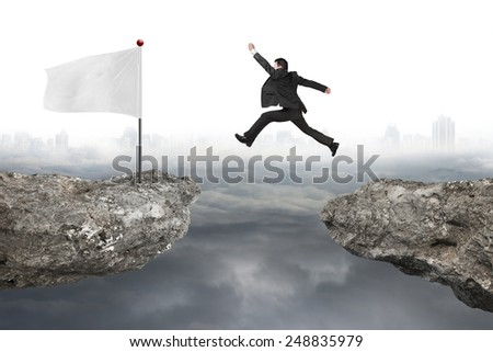 Businessman jump on cliff with blank white flag and gray cloudy cityscape background - stock photo
