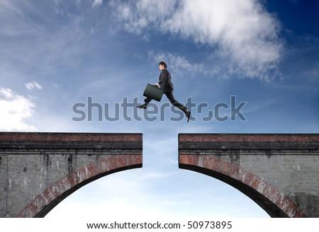 Businessman jumping a gap between two bridge parts - stock photo