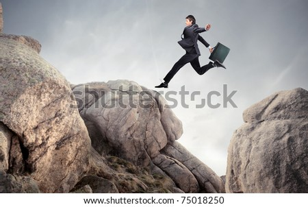 Businessman jumping from a stone to another