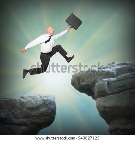 Businessman jumping from high cliff to the unknown. Victory and success or suicide, risk in business. Man and his career concept or enter to New year for all metaphor.