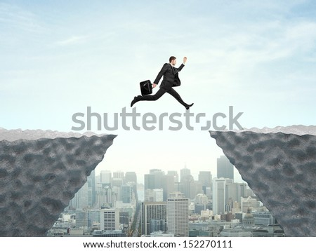 businessman jumping from rock to another rock - stock photo