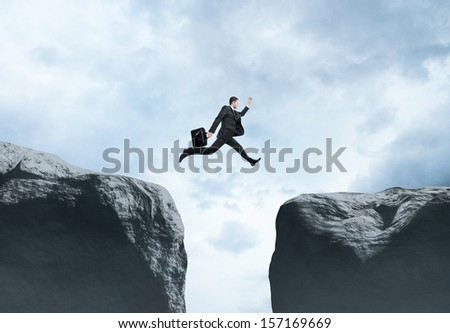 businessman jumping  from rock to rock - stock photo