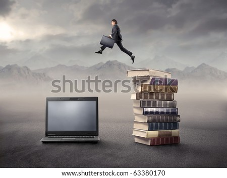 Businessman jumping from some books to a laptop in a desert - stock photo