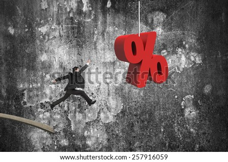 Businessman jumping from wooden board to red percentage sign with mottled concrete wall background - stock photo