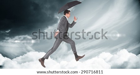 Businessman jumping holding an umbrella against blue sky