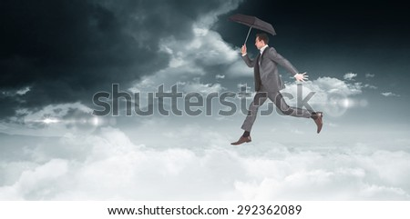 Businessman jumping holding an umbrella against bright blue sky with clouds - stock photo