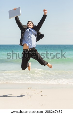 Businessman jumping in front of the sea at the beach - stock photo