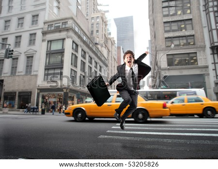 Businessman jumping on a city street - stock photo