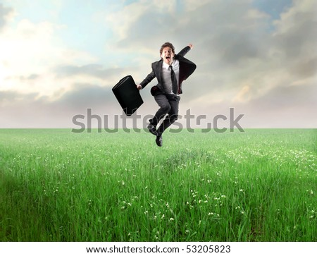 Businessman jumping on a green meadow - stock photo