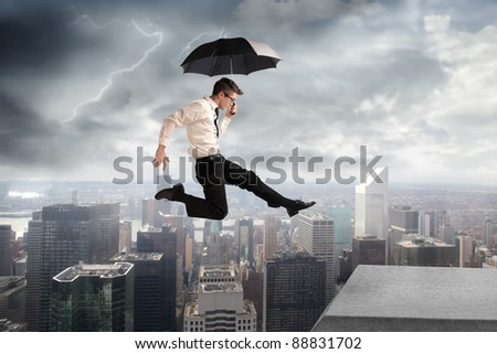 Businessman jumping on a skyscraper with cityscape under stormy sky in the background