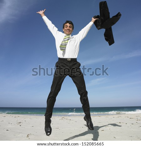 Businessman jumping on beach