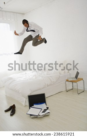 Businessman Jumping on Bed - stock photo