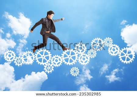 Businessman jumping on sketch gear system. - stock photo