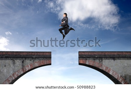 Businessman jumping over an empty space - stock photo