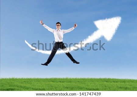 Businessman jumping over success arrow cloud sign outdoor while giving hit thumbs up - stock photo