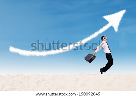 Businessman jumping under increase arrow sign  - stock photo