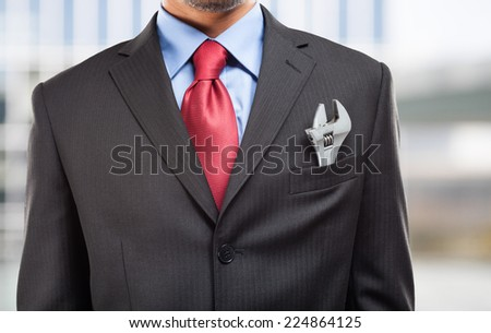 Businessman keeping an adjustable wrench in his pocket - stock photo