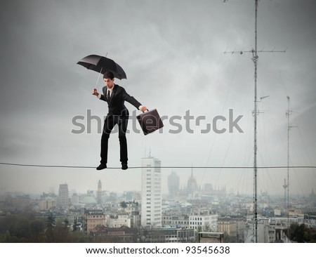 Businessman keeping his balance on a rope over a big city